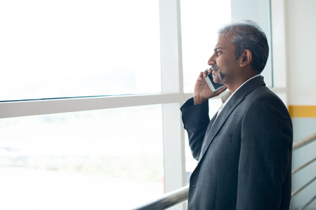 old asian: matured indian business male using  smartphone Stock Photo