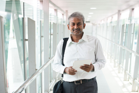 mid thirties: indian businessman outdoor with a computer tablet