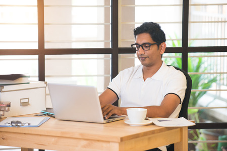 laptop computer: casual indian male working at office Stock Photo