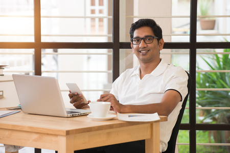 men at work: young indian man working from home office Stock Photo