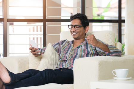 casual indian male using phone at livingroom