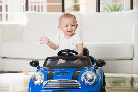 Aziatische baby het berijden van een speelgoedauto Stockfoto