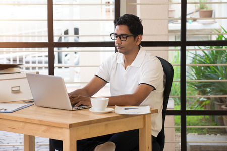 pakistani ethnicity: young indian man working from home office Stock Photo
