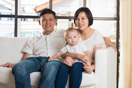 family  room: Happy Asian Family Playing with baby in the living room
