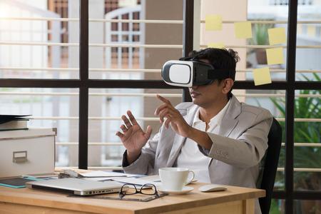 virtual technology: indian male using virtual reality technology at work Stock Photo