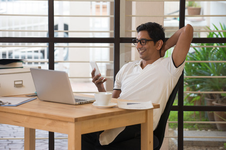 pakistani ethnicity: indian man using smartphone at office while smiling