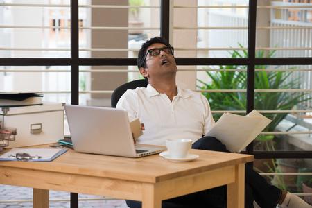 sleepy indian man at office