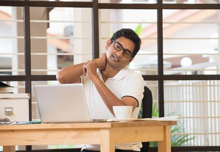 usando computadora: Hombre indio ocasional estiramiento en la oficina Foto de archivo