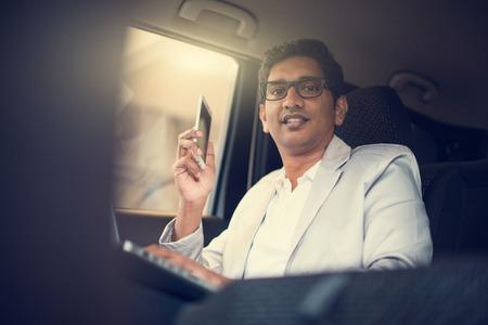 asiento: Hombres de negocios india que usa el ordenador portátil y el teléfono dentro del coche
