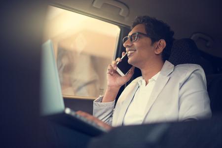 ノート パソコンと車の中の携帯電話を使用してインドのビジネス男性
