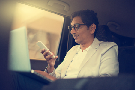 businessman phone: indian business male using laptop inside the car