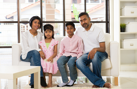 two children: happy indian family at living room