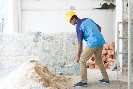cement pile: indian male contractor using shovel Stock Photo