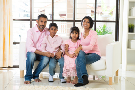 padres e hijos felices: familia feliz indio en la sala de estar Foto de archivo
