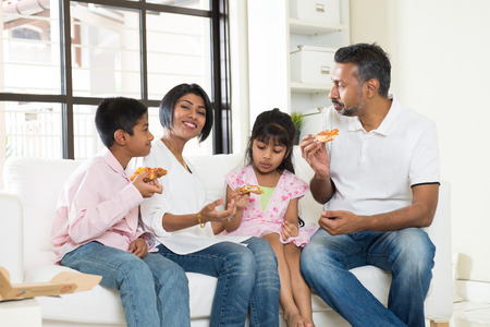 family together: happy indian family eating pizza at home