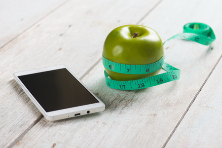 weight loss plan: blank smartphone with green apple and tape