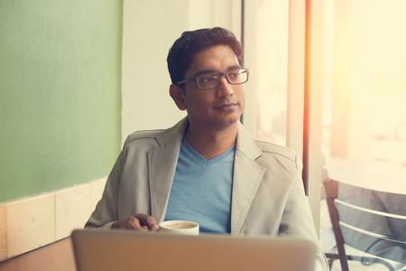 persona leyendo: el consumo de café indio masculino