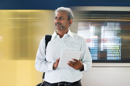 indian male taking subway to work on internet tablet