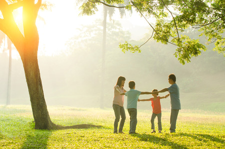 Happy young family having fun outside in summer nature photo