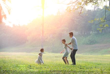 公園で家族との時間を一緒に楽しんで幸せなアジア家族   写真素材