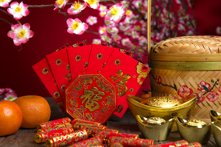 prosper: Chinese new year festival decorations, ang pow or red packet and gold ingots. Stock Photo