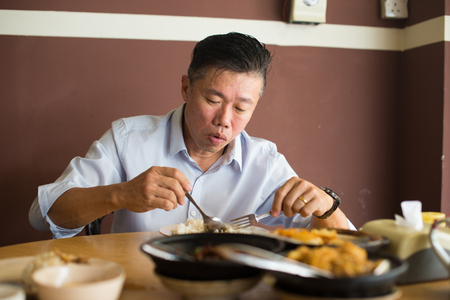 asian matured male eating bah kut teh