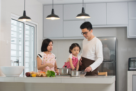 family together: asian family cooking at kitchen