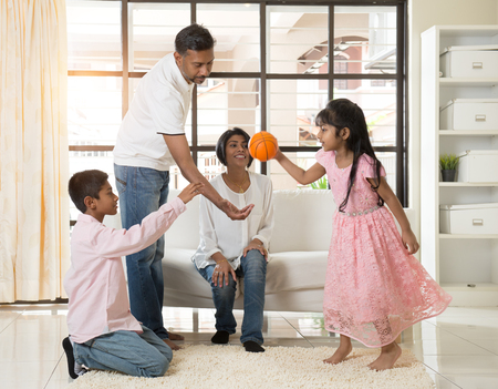 family time: indian family playing with ball in living room