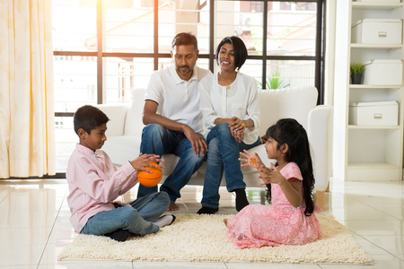 indian family playing with ball in living room photo
