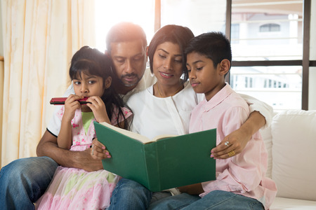 indian family reading a book together photo