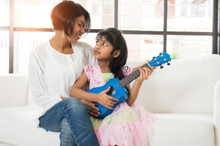indian mother and daughter playing ukulele photo
