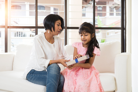 indian mother and daughter giving present photo