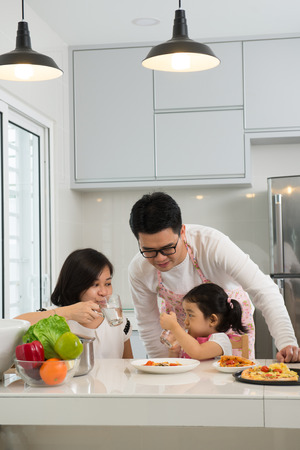asian family enjoying and cooking pizza Stock Photo