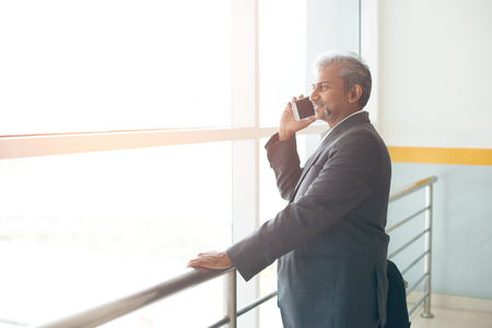indian business male using phone at the airport