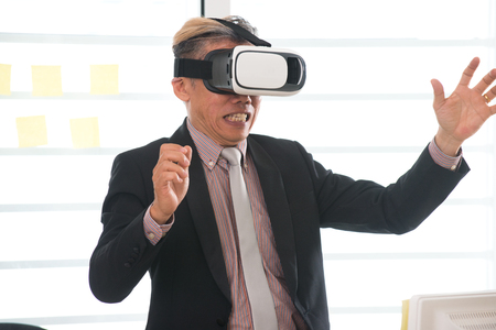 singaporean: Businessman making gestures when wearing virtual reality goggles Stock Photo