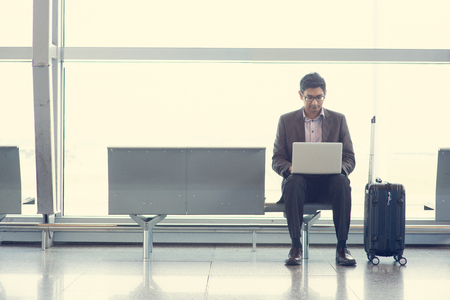 internet terminal: Asian Indian business man sitting on chair and using laptop while waiting his flight at airport.
