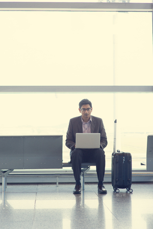 Asian Indian business man sitting on chair and using laptop while waiting his flight at airport. photo