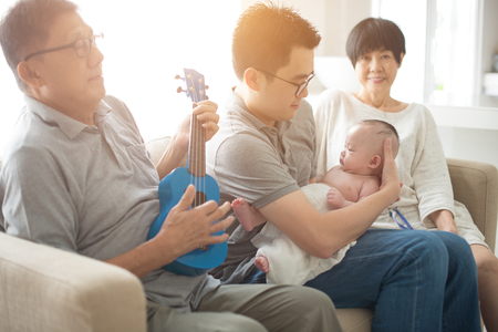 asian grandparent playing music with father and baby boy indoor photo