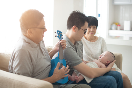 asian grandparent playing music with father and baby indoor