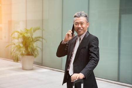 asian senior businessman travel with phone