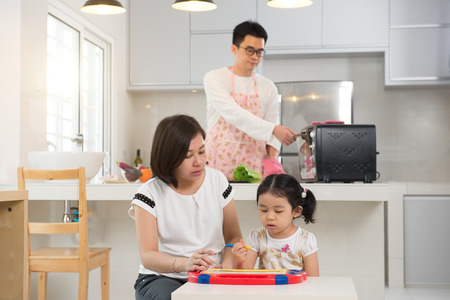 asian mother teaching daughter while father cooking