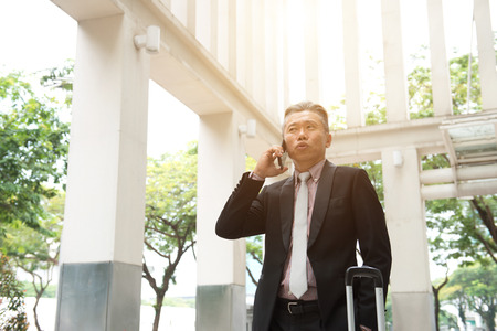 asian senior businessman travel with phone   Stock Photo
