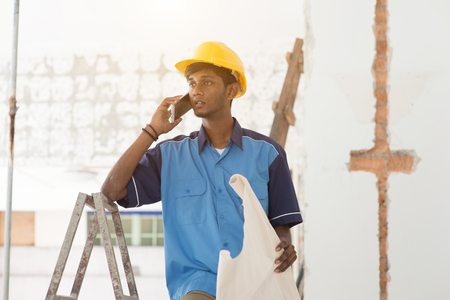 indian male construction worker using phone