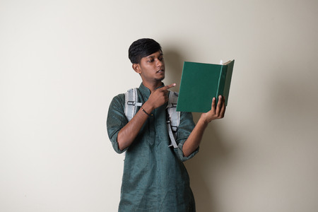 teenage indian male in traditional dress reading books