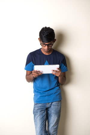indian teenage male on tablet computer Stock Photo