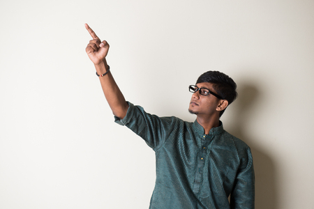 teenage indian male in traditional dress pointing somewhere Stock Photo