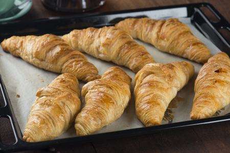 Fresh Croissants on rustic wooden background. Selective focus, horizontal.