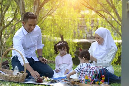 moslim maleis familie genieten van picknick in het park Stockfoto
