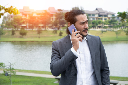 attractive mixed middle eastern looking business man with a phone