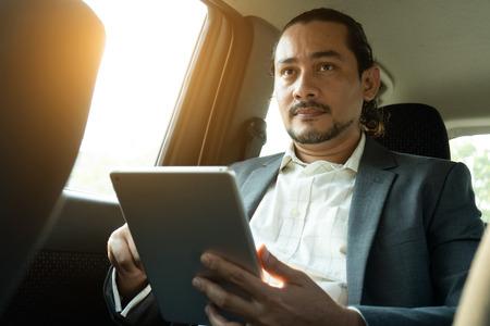 middle eastern businessman inside a car passenger
